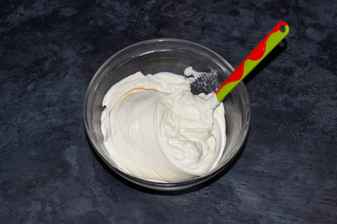 Baileys whipped cream being folded into cream cheese in a glass bowl with a green spatula
