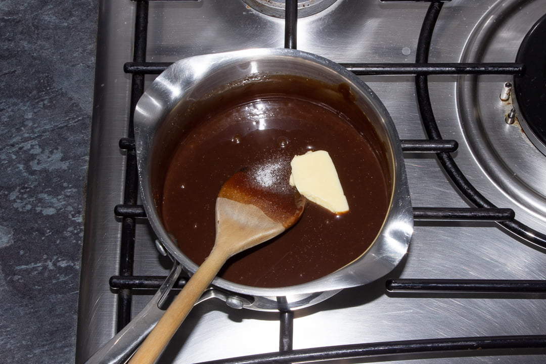 Baileys milk chocolate sauce in a saucepan over a low heat with butter and salt being stirred through