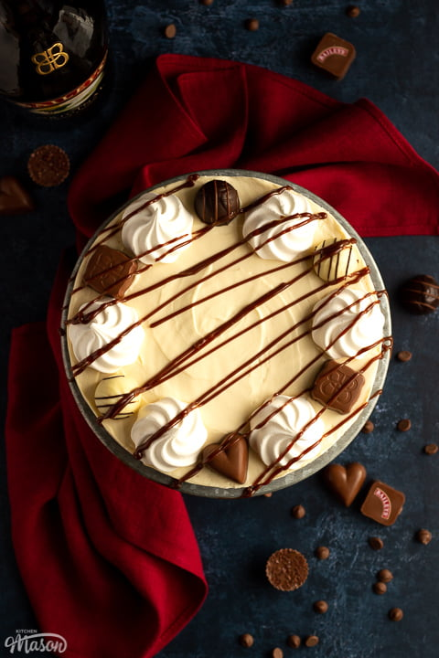 Flat lay view of a Baileys cheesecake on a cake stand set over a deep blue background with a red linen napkin. There are Baileys chocolates and chocolate chips scattered around.