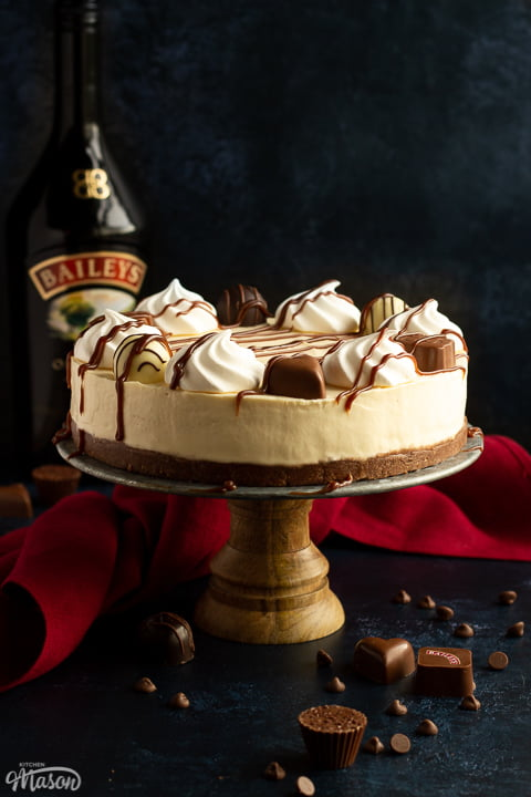 Baileys cheesecake on a cake stand set over a deep blue background with a red linen napkin. A bottle of Baileys sits in the background and Baileys chocolates/chocolate chips are scattered around