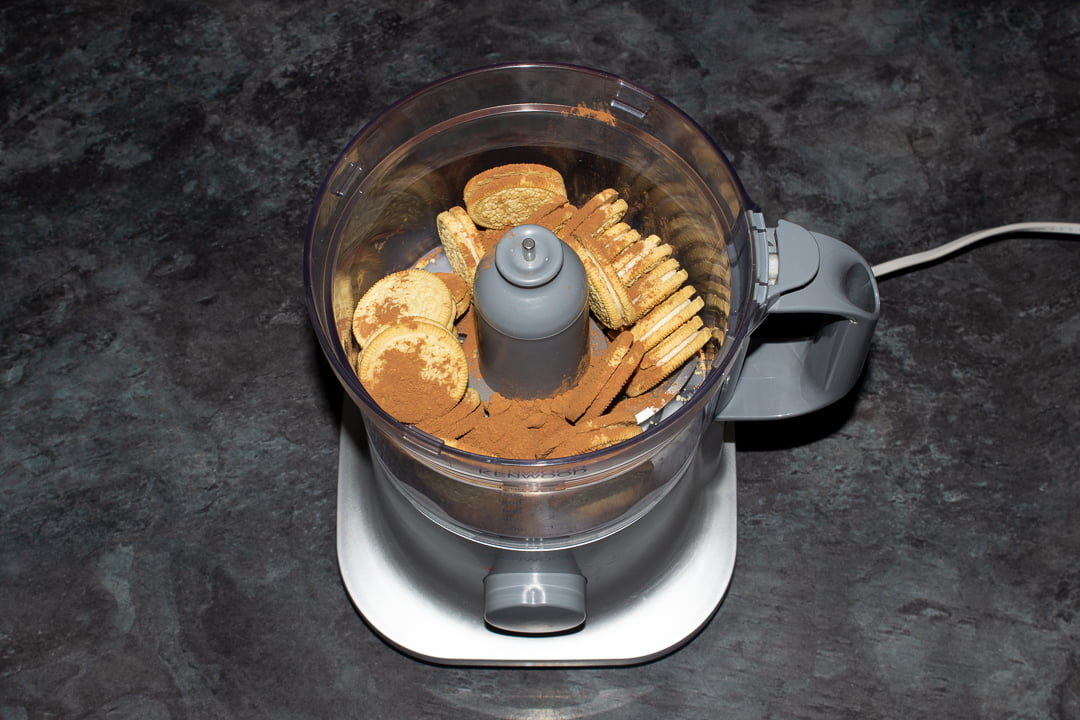 Golden Oreos and cocoa powder in a food processor ready for blending