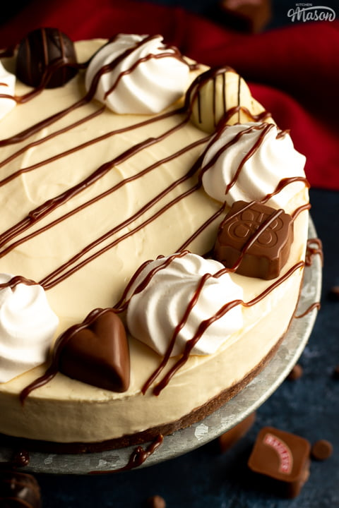 A close up of a no bake Baileys cheesecake on a cake stand set over a blue background with a red linen napkin