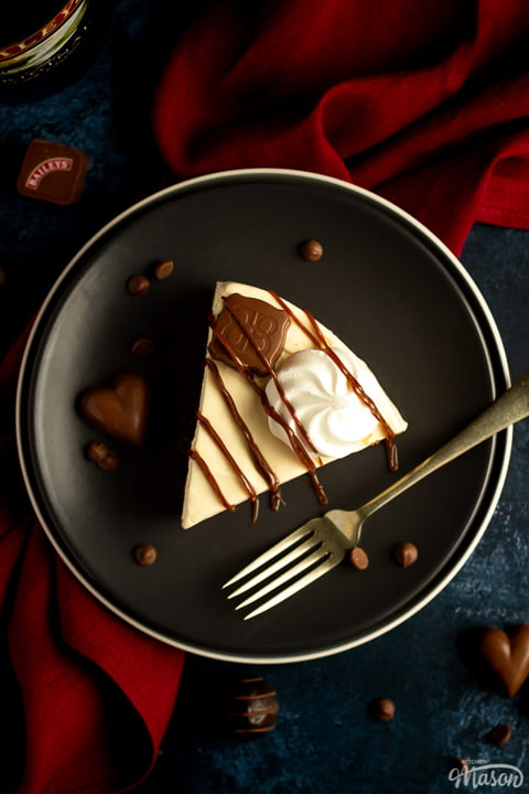 A slice of no bake Baileys cheesecake on a dark grey plate with a fork that's set over a deep blue background and a red linen napkin. There's a bottle of Baileys in the back and Baileys chocolates / chocolate chips scattered around.