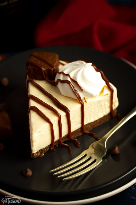 A slice of no bake Baileys cheesecake on a dark grey plate with a fork that's set over a deep blue background and a red linen napkin. There's Baileys chocolates and chocolate chips scattered around.