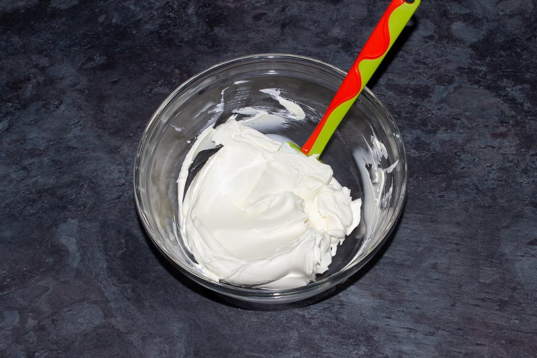 Cream cheese that's been beaten slightly to soften it in a glass bowl with a green spatula