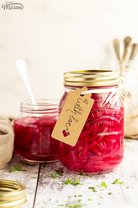 A sealed jar of pickled red onions with a label tied to it that says 'with love'. Sat on a rustic white wood backdrop with an open jar of pickled red onions, a light brown napkin, a pickling jar lid and a jar of cutlery in the background.