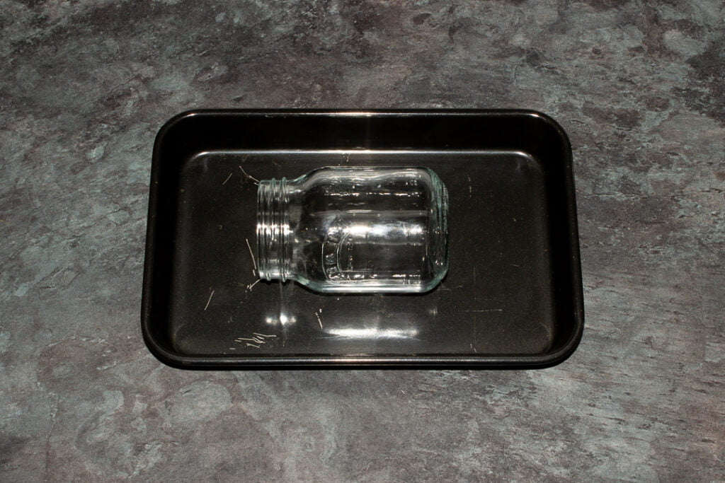 a glass jar on a black baking tray ready for sterilising in the oven