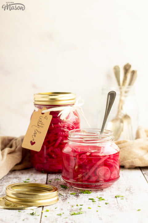 An open jar of pickled red onions with a fork in. Sat on a rustic white wood backdrop with a sealed and labelled jar of pickled red onions, a pickling lid, a jar of cutlery and a light brown napkin in the background.