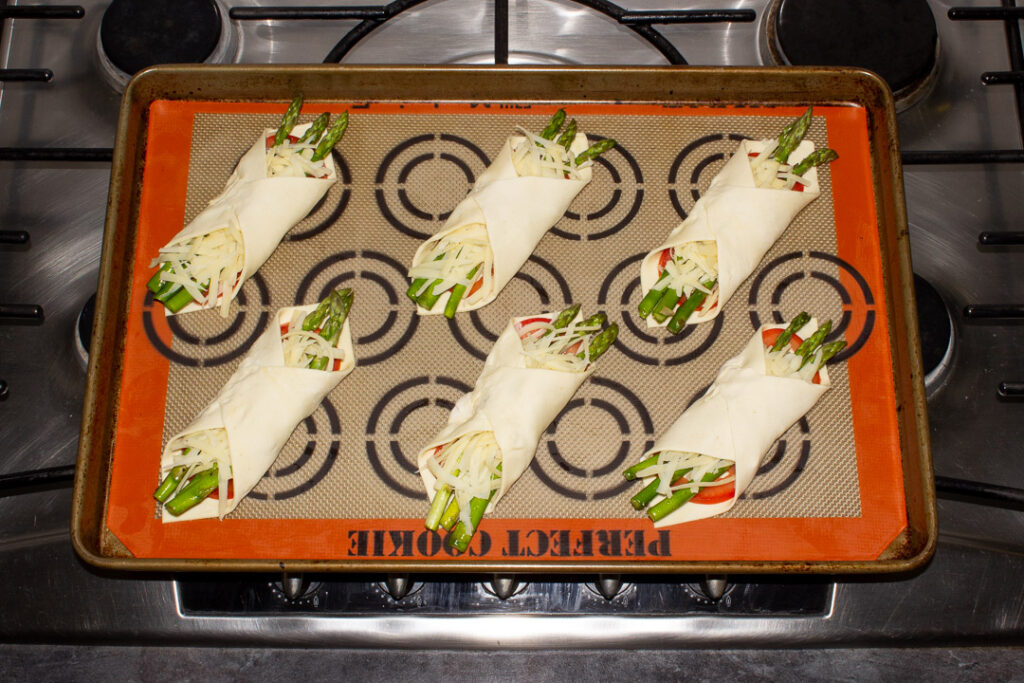 6 asparagus puff pastry parcels on a lined baking tray