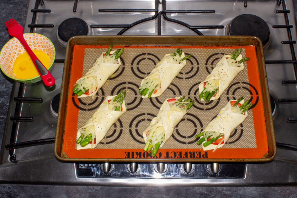 6 asparagus puff pastry parcels on a lined baking tray being brushed with beaten egg and scattered with freshly ground pepper