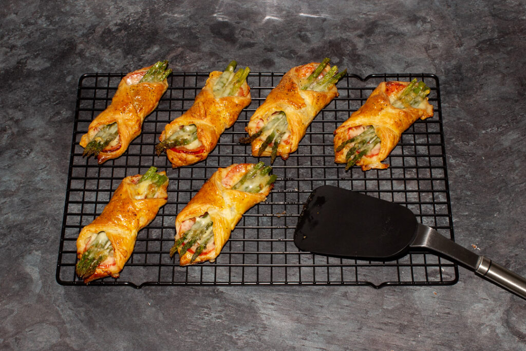 6 baked asparagus puff pastry parcels on a wire rack with a rubber spatula