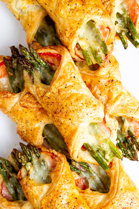 A close up of some asparagus puff pastry parcels on a white serving plate
