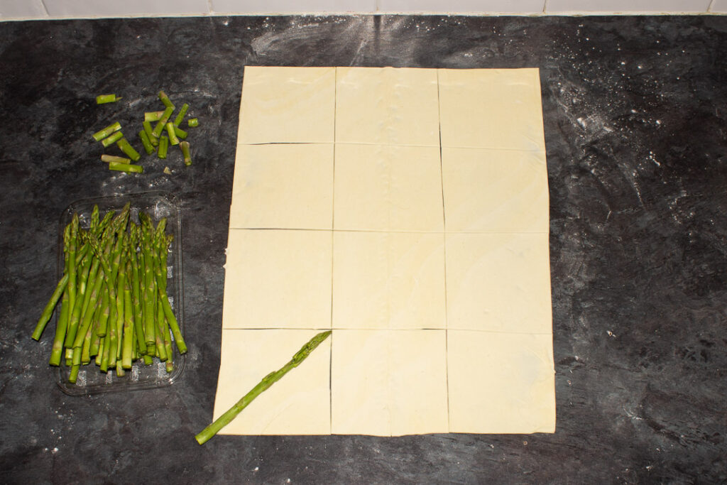 A sheet of ready rolled puff pastry cur into squares on a lightly floured work surface. There are asparagus tips being cut to size too.