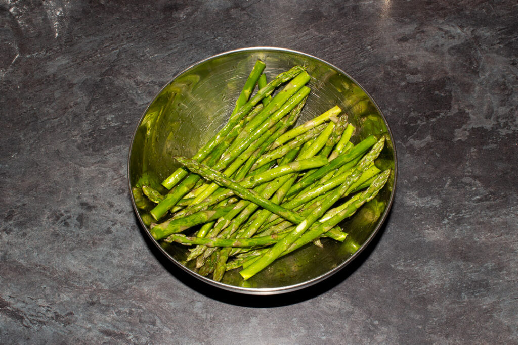 Asparagus tips coated in olive oil, salt and pepper in a metal bowl on a work surface