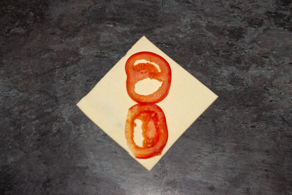 A square of puff pastry on the diagonal with two thin slices of tomato on top