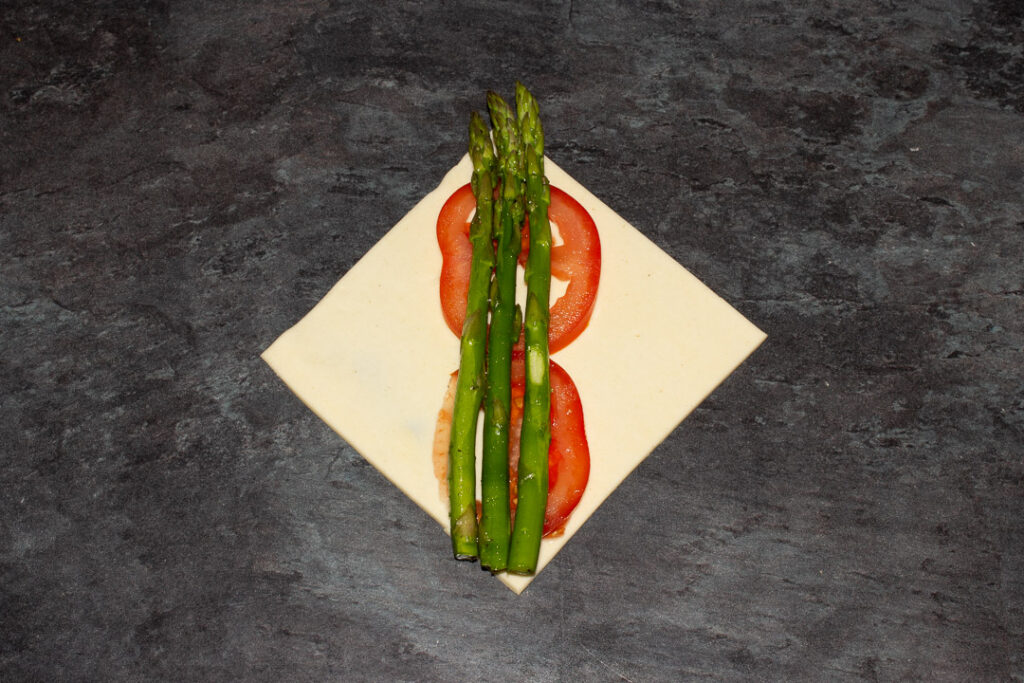 A square of puff pastry on the diagonal with two thin slices of tomato on top and 3 trimmed asparagus tips