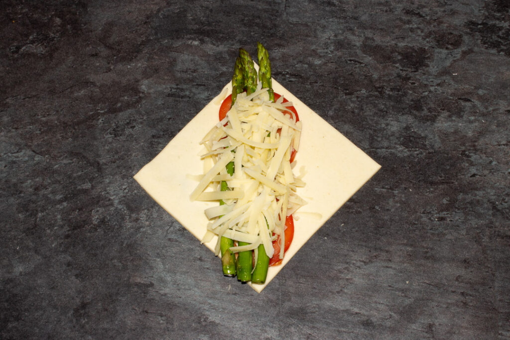 A square of puff pastry on the diagonal with two thin slices of tomato on top, 3 trimmed asparagus tips and a little grated gruyere cheese