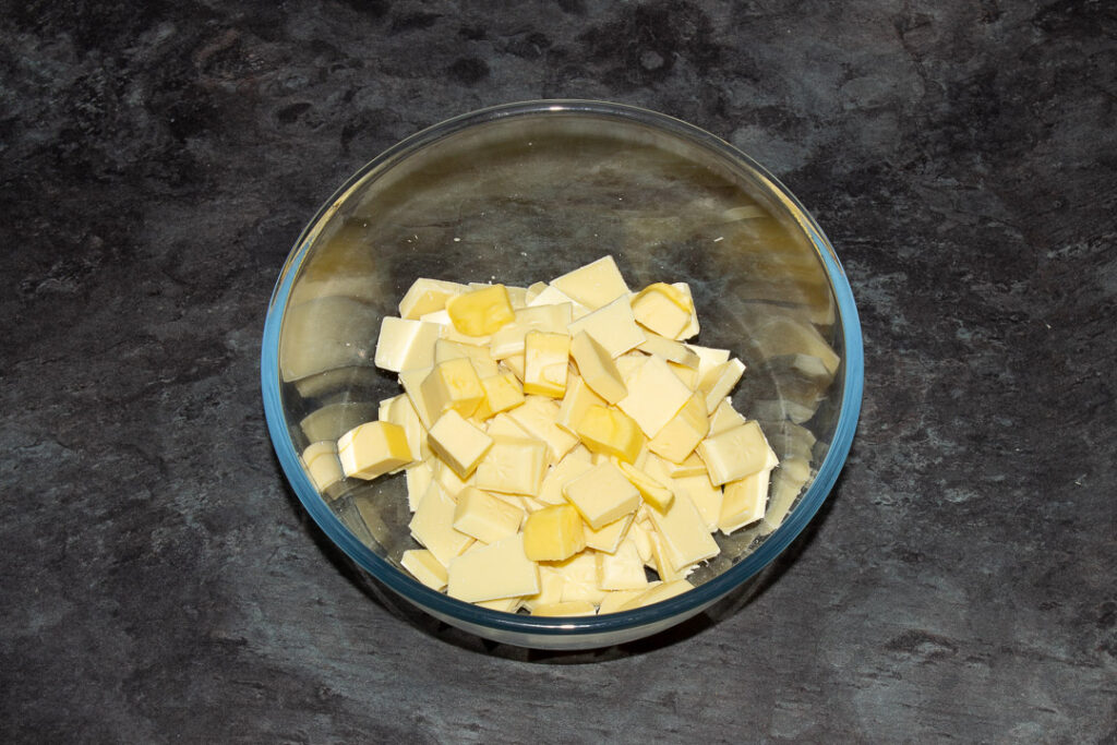 butter and white chocolate in a glass bowl on a kitchen worktop