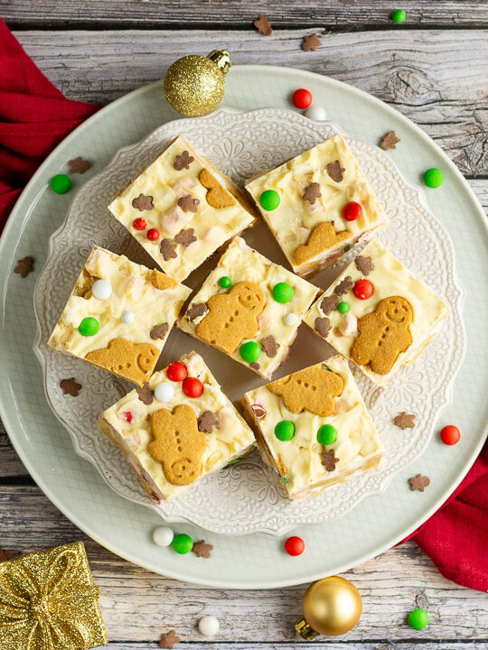 Christmas rocky road squares on a lace white plate set on a red linen napkin over a grey wood backdrop. There are Christmas sprinkles, gold baubles and decorations scattered around.