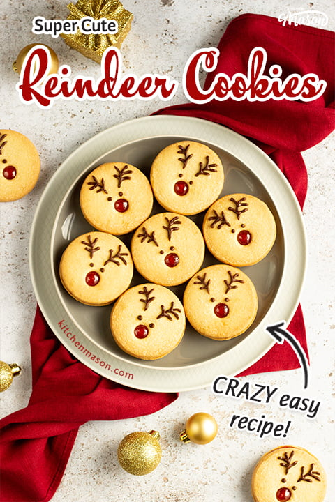 A plate of Reindeer cookies set on a second plate and a red linen napkin. Set on an off white backdrop with golden baubles, golden presents and more reindeer cookies in the background.