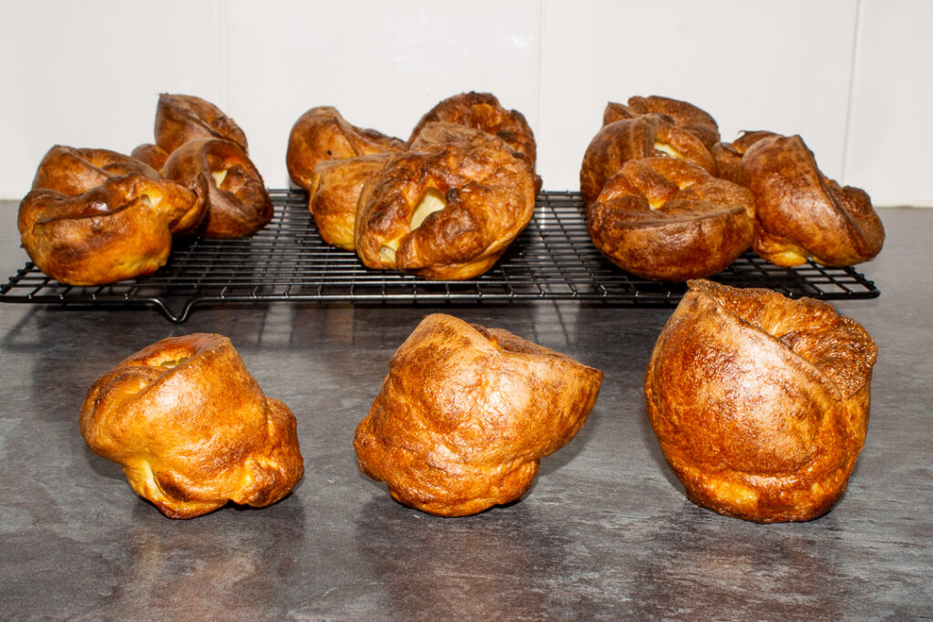 Yorkshire puddings on a wire cooling rack with 3 in front showing the size effect that different resting times have.
