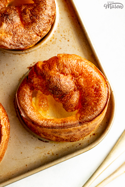 Yorkshire puddings in a Yorkshire pudding pan with a fork in the background.