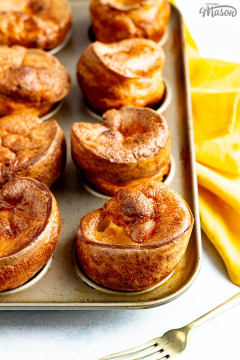 Yorkshire puddings in a Yorkshire pudding pan with a mustard yellow napkin and a fork in the background.