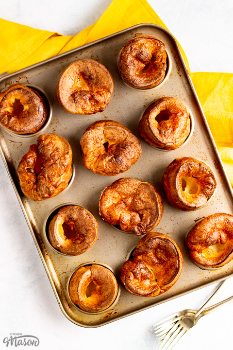 Birds eye view of Yorkshire puddings in a Yorkshire pudding pan with a mustard yellow napkin and 2 forks in the background.
