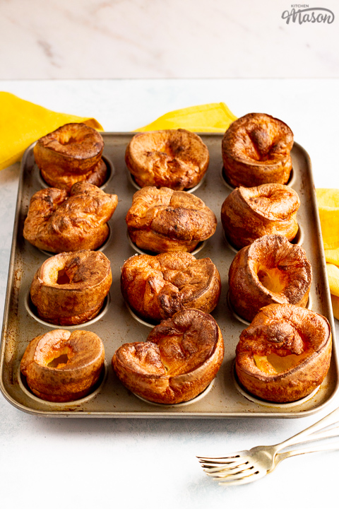 Yorkshire puddings in a Yorkshire pudding pan with a mustard yellow napkin and 2 forks in the background.