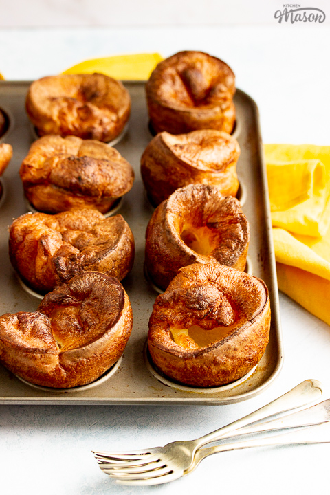 Yorkshire puddings in a Yorkshire pudding pan with a mustard yellow napkin and 3 forks in the background.