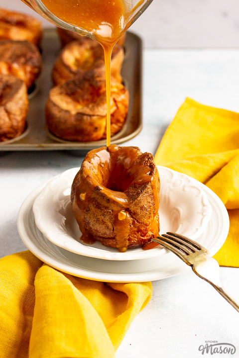 A Yorkshire pudding with gravy being poured over it in a small white bowl set over a mustard yellow napkin. There's a fork resting on the bowl and more Yorkshire puddings in a Yorkshire pudding tin in the background.