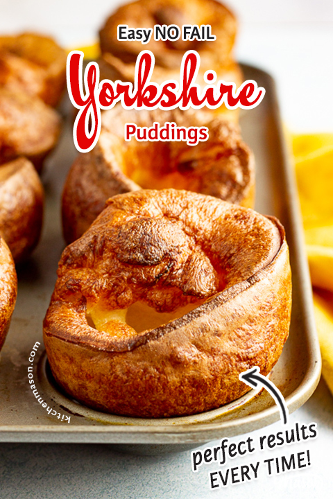 Yorkshire puddings in a Yorkshire pudding pan with a mustard yellow napkin in the background.