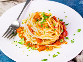 A close up side view of a nest of fresh tomato spaghetti on a white plate scattered with chopped parsley. There's a fork resting on the plate and a light brown napkin in the background, all set on a blue backdrop.