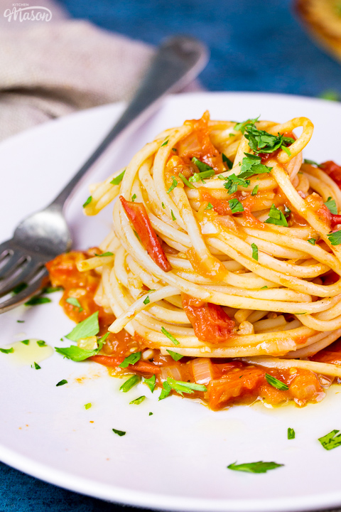 A close up side view of a nest of tomato spaghetti on a white plate scattered with chopped parsley. There's a fork resting on the plate and it's set on a blue backdrop.