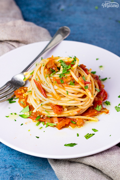 A side view of a nest of fresh tomato spaghetti on a white plate scattered with chopped parsley. There's a fork resting on the plate and a light brown napkin in the background, all set on a blue backdrop.