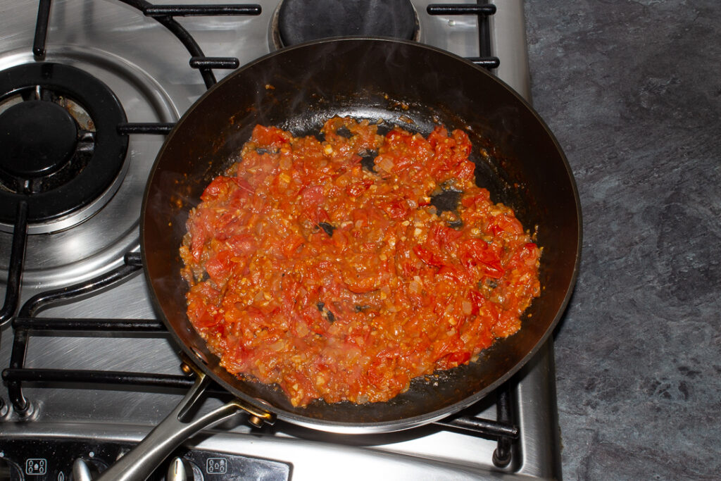 Cooked and reduced onion, garlic, cherry tomatoes, balsamic vinegar and salt and pepper in a frying pan on the stove