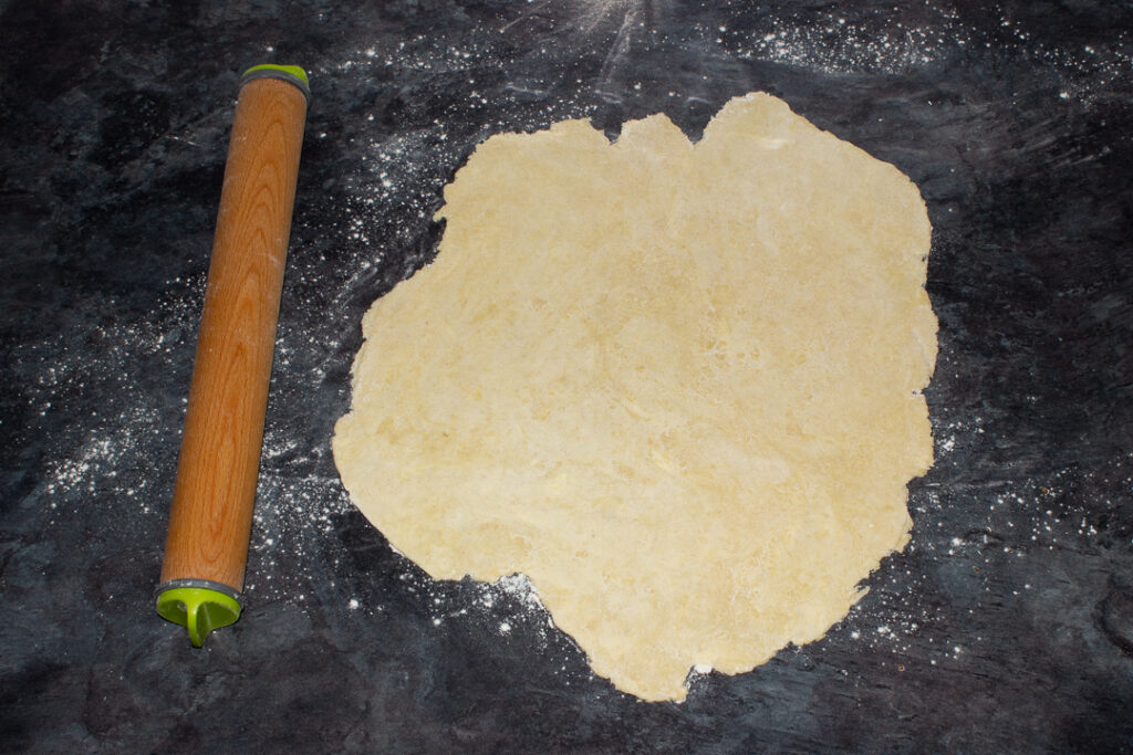 Shortcrust pastry rolled out on a floured worktop with a rolling pin