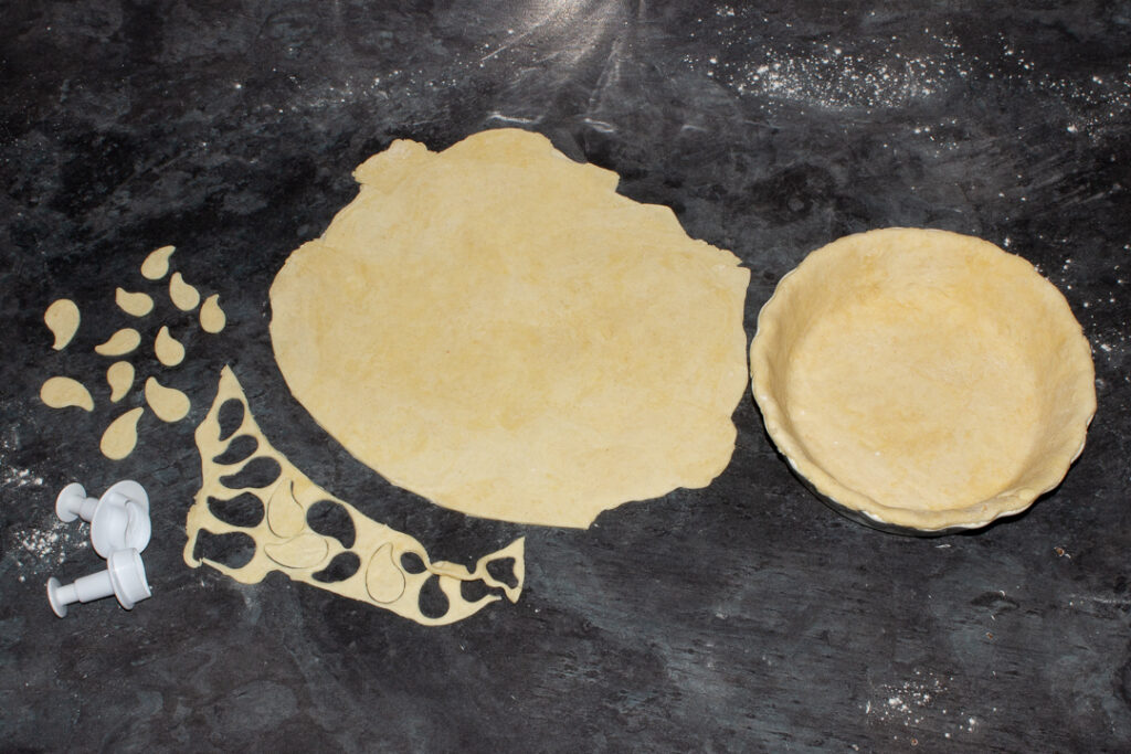 A pie dish lined with shortcrust pastry, remaining pastry rolled out ready to cut the pie lid and some pastry scraps having leaves cut out of them, all on a floured worktop