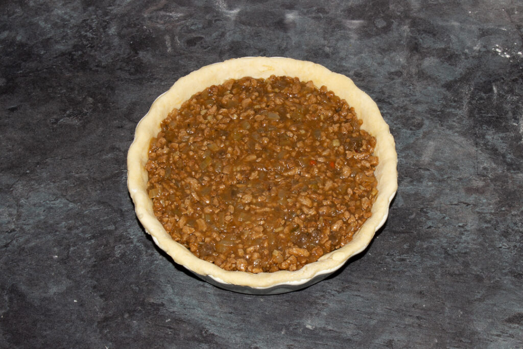 A pie dish lined with shortcrust pastry filled with vegetarian soya mince and onion