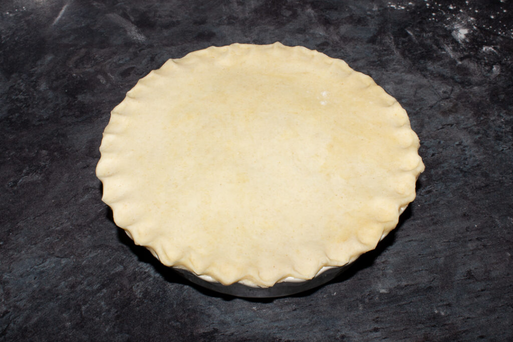 An unbaked vegetarian mince and onion pie with crimped edges