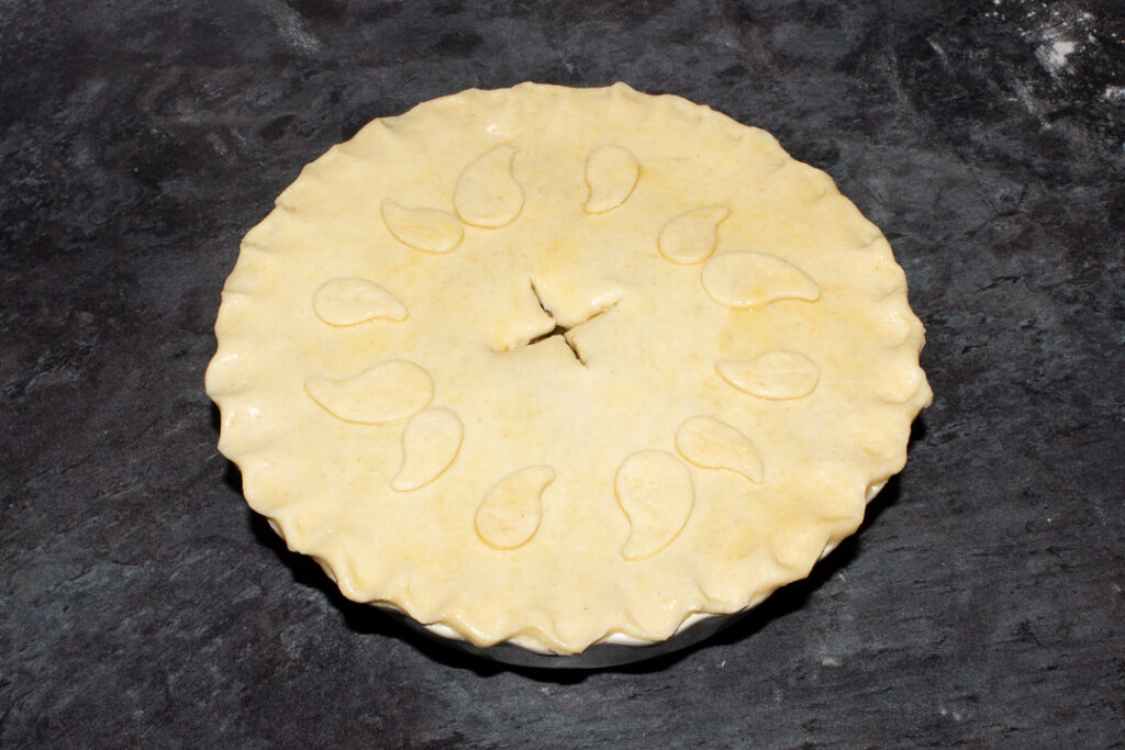 An unbaked vegetarian mince and onion pie with crimped edges, decorated with pastry leaves and brushed all over with egg
