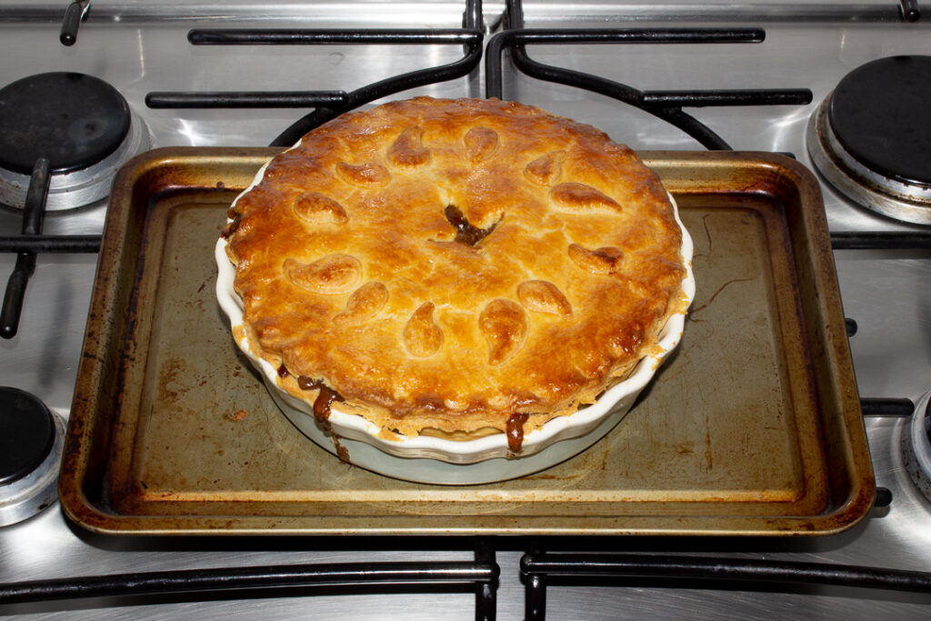 A baked vegetarian mince and onion pie on a baking tray on the stove top