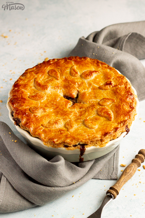 A baked vegetarian mince and onion pie decorated with pastry leaves sat on a grey linen napkin with a wooden handled fork. Set on a pale blue wash backdrop.