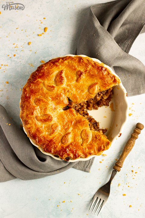 A baked vegetarian mince and onion pie with a slice cut out, decorated with pastry leaves, sat on a grey linen napkin with a wooden handled fork. Set on a pale blue wash backdrop.