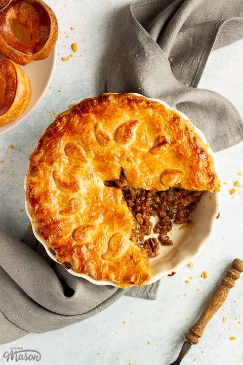 A baked vegetarian mince and onion pie with a slice cut out, decorated with pastry leaves, sat on a grey linen napkin. There's a wooden handled fork and a plate of Yorkshire puddings in the background. Set on a pale blue wash backdrop.