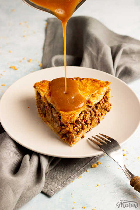 A slice of vegetarian mince and onion pie on a light grey plate with a wooden handled fork resting on it and gravy being poured onto it. Set on a grey linen napkin over a pale blue wash backdrop.