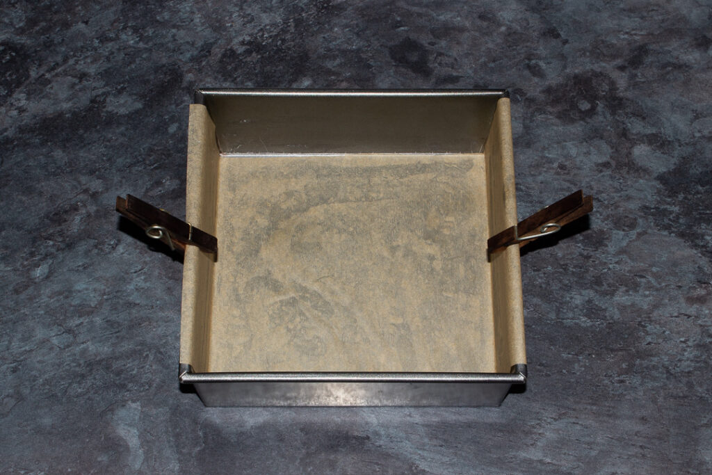 A square baking tin lined with baking paper and held on by two pegs