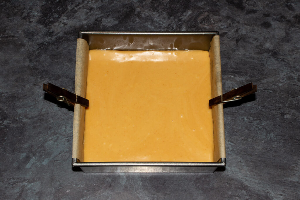 A lined square baking tin with caramel poured over red velvet brownie.