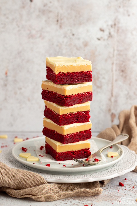 A stack of 5 red velvet millionaire brownies set on two stacked plates with a fork on the side. There are white chocolate hearts, red velvet brownie crumbs and a light brown napkin in the background.