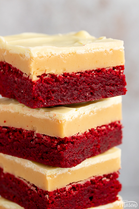 A close up of 4 red velvet millionaire brownies in a stack set against a mottled light background.